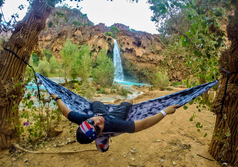 Young man leaning back in his hammock, hung between two trees in front of a waterfall