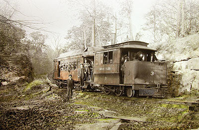 Black and White image depicting a 19th century train filled with passengers and a man standing next to it, in the woods