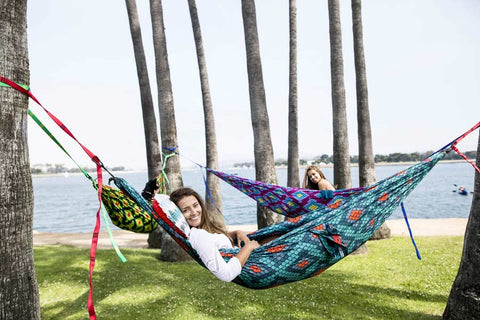 group of girls hammocking by the water and smiling
