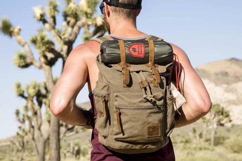 man wearing a brown backpack in the desert