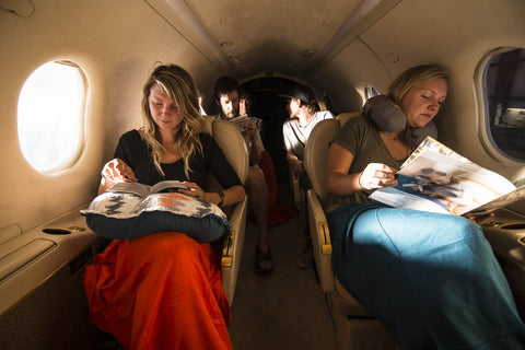two women on a plane reading books