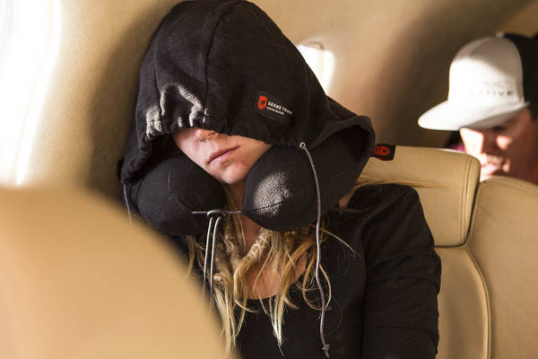 woman sleeping on a plane wearing a black hooded travel pillow