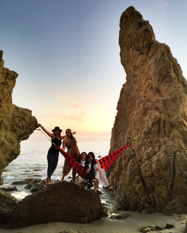 group of girls hammocking on the beach between two large rocks