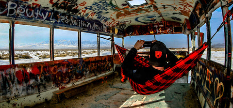 man sitting in a hammock inside of a spray painted bus