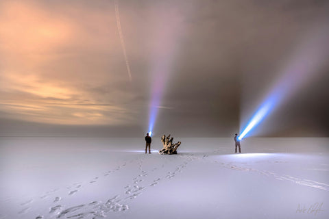 Two people shining flashlights in a snowcovered plain