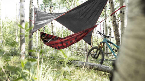 man sleeping in a red and black hammock in the woods
