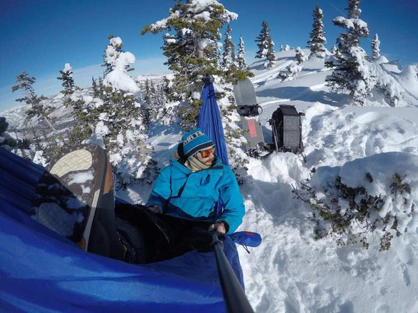 man hammocking in the snow on a mountain