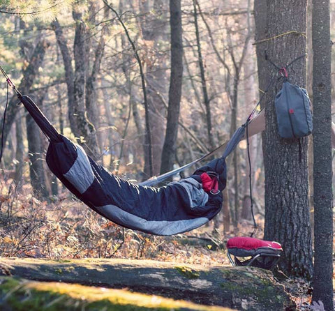 sleeping bag hammock hung between two trees
