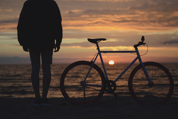 person standing next to a bicycle on the beach staring at the sun setting over the water
