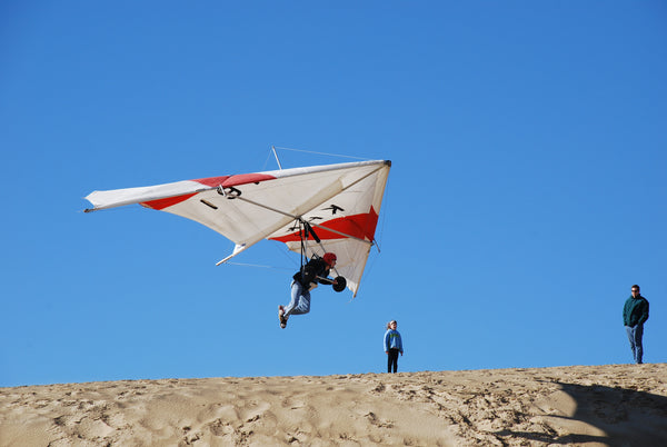 person hang gliding above a sand dune