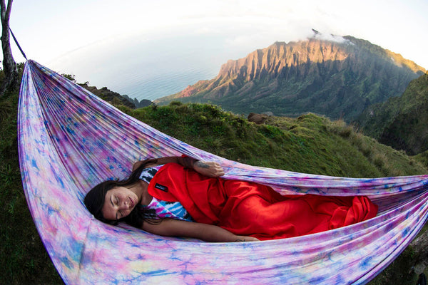 a girl sleeping in a pink tie-dye hammock