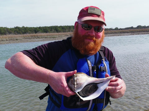 Man with a large, bushy red beard holding a conch shell at Huntington Beach State Park, South Carolina