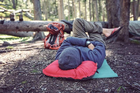 woman resting her head on a fluffy travel pillow in the woods
