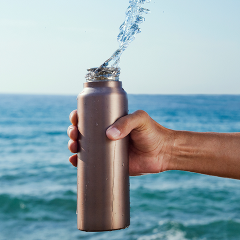 A person holding a tin reusable water bottle with water splashing upwards.