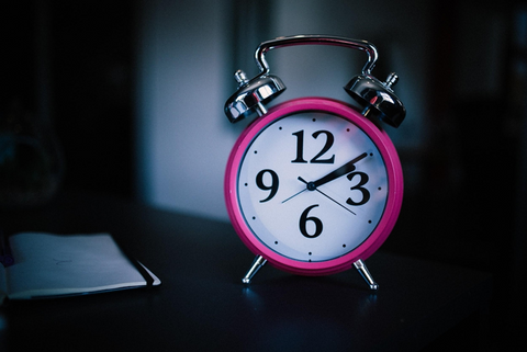 A pink analog alarm clock sitting on a night stand.