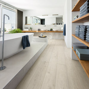 Modern bathroom with open shelves, raised tub and wide plank laminate flooring