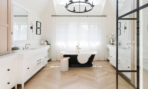 Chevron engineered hardwood installed in a luxurious bathroom with black pedestal soaker tub white walls and high ceiling
