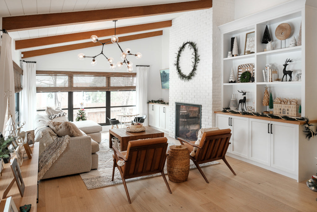 Living room with wooden ceiling beams exposed brick fireplace painted white and natural white oak hardwood floors