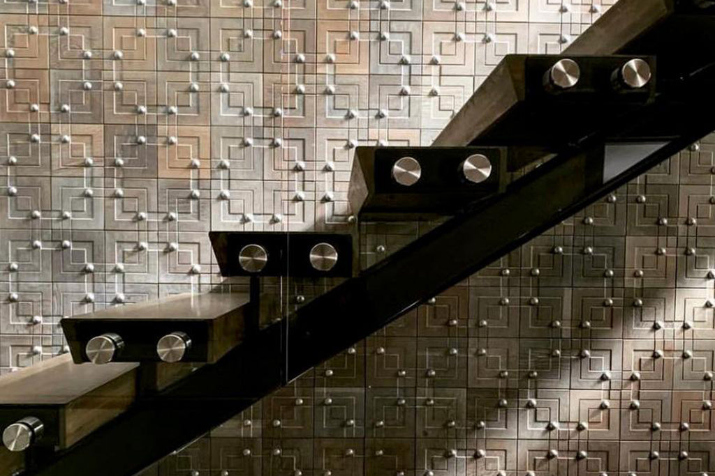 Metal nail heads adorn the sculpted wooden surface in this modern and luxurious staircase
