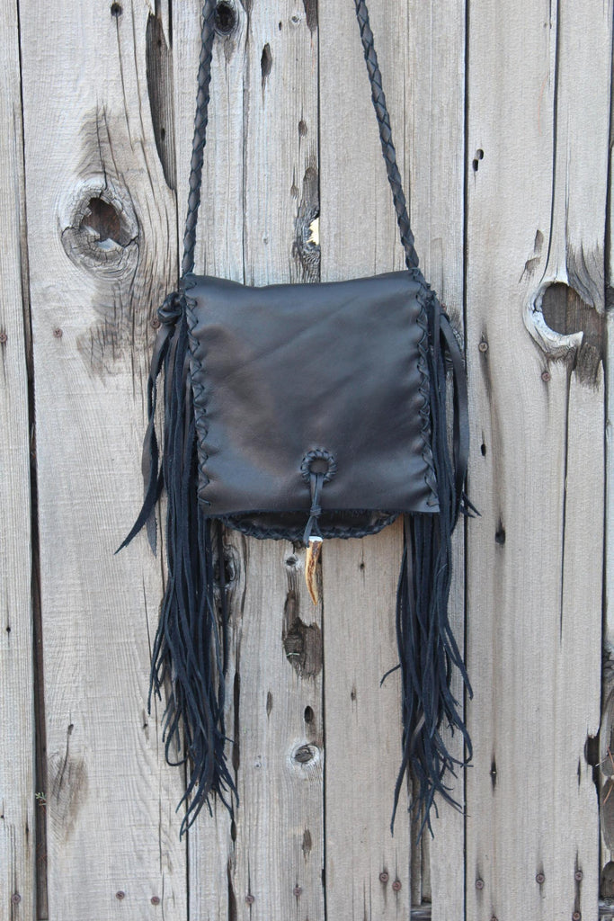 Black leather handbag with fringe and an antler tip closure