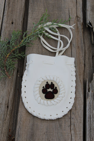White buckskin medicine bag with beaded wolf paw totem