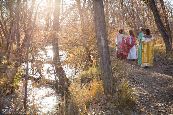 four women dressed in corsets and flowing robes walk near a stream in late afternoon autumn light