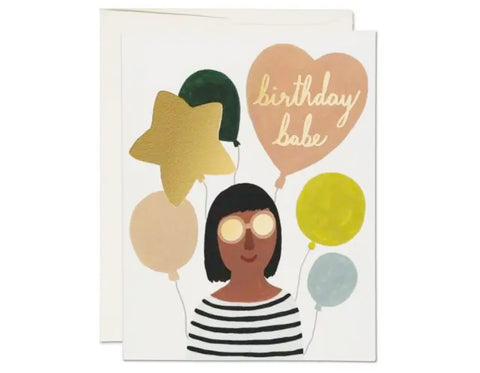 woman with short black hair and bangs and ballons. heart shaped balloon says birthday babe in cursive.