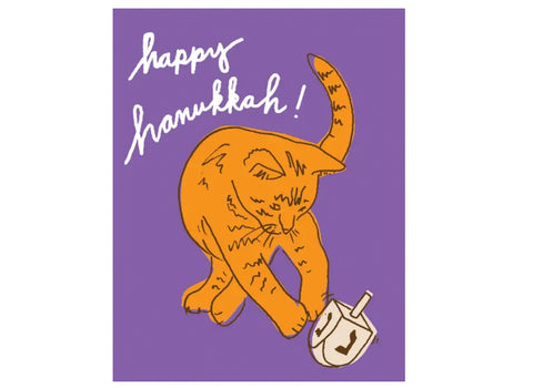 purple background, orange cat playing with dreidel, text reads happy hanukkah!