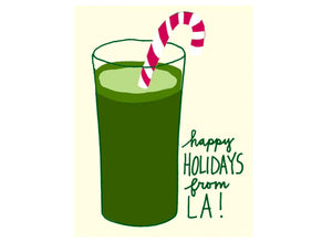green juice with candy cane in it reads happy holidays from la!
