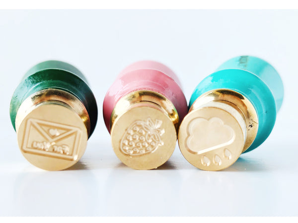 mini brass seals an envelope with a heart and the words for you, a strawberry, and a cloud with raindrops