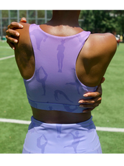 Photo of Lukafit founder standing in a park with her back to the camera, with her arms embracing herself. We can see from the back of her neck down to her waist. She is wearing the Lukafit standout sports bra and squat-proof leggings. Her bra and leggings are both lavender ombre color with our signature print of women doing different yoga and workout poses.