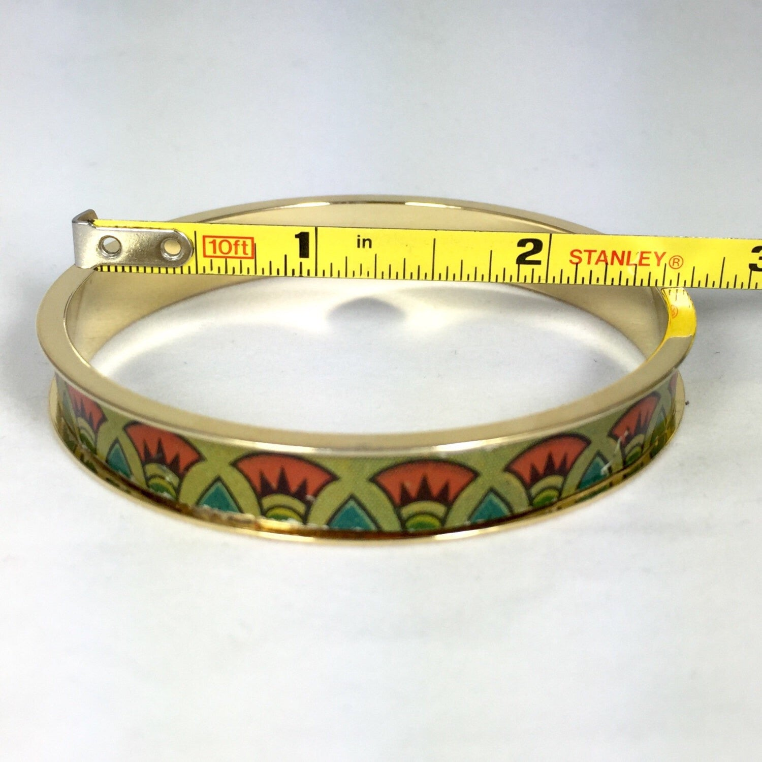 2- 24kt gold plated bangle fitted with a with vintage tin inlay.  The biscuit tin design includes Egyptian style red and green flowers.  The inside measurement of the bangles is approximately 7 3/4''. around.