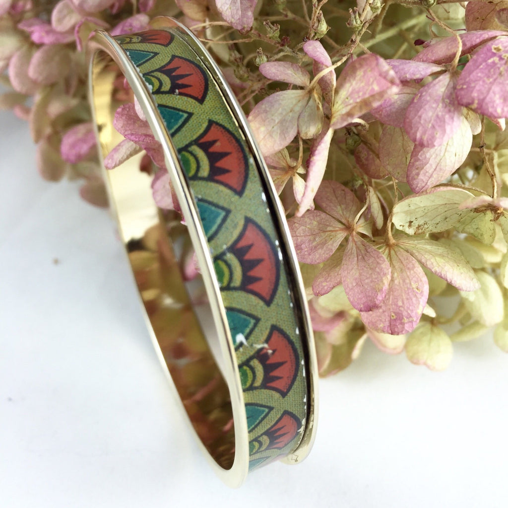 24kt gold plated bangle fitted with a with vintage tin inlay.  The biscuit tin design includes Egyptian style red and green flowers.  The inside measurement of the bangles is approximately 7 3/4''. around.