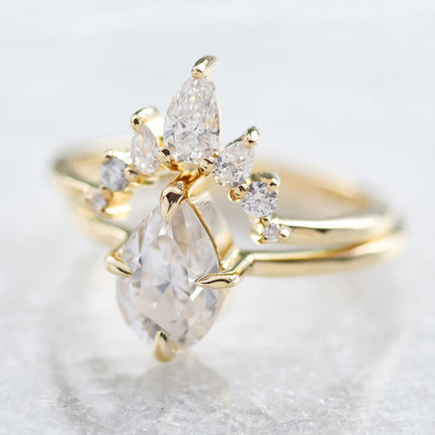 A diamond contour band and diamond solitaire engagement ring