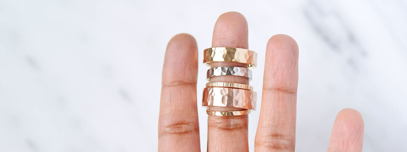 Hammered bands in yellow gold, rose gold and white gold on a hand