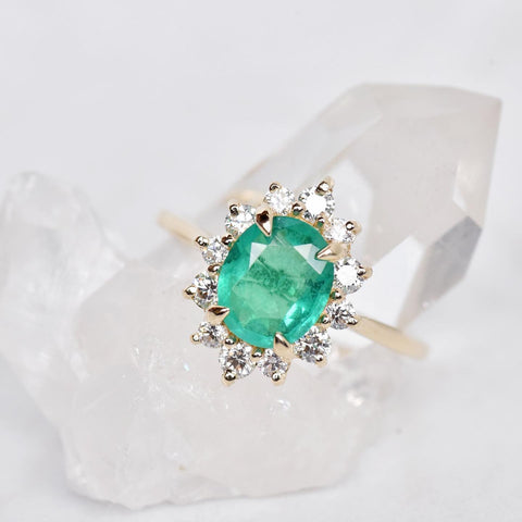 An Emerald Marisol halo engagement ring on a crystal