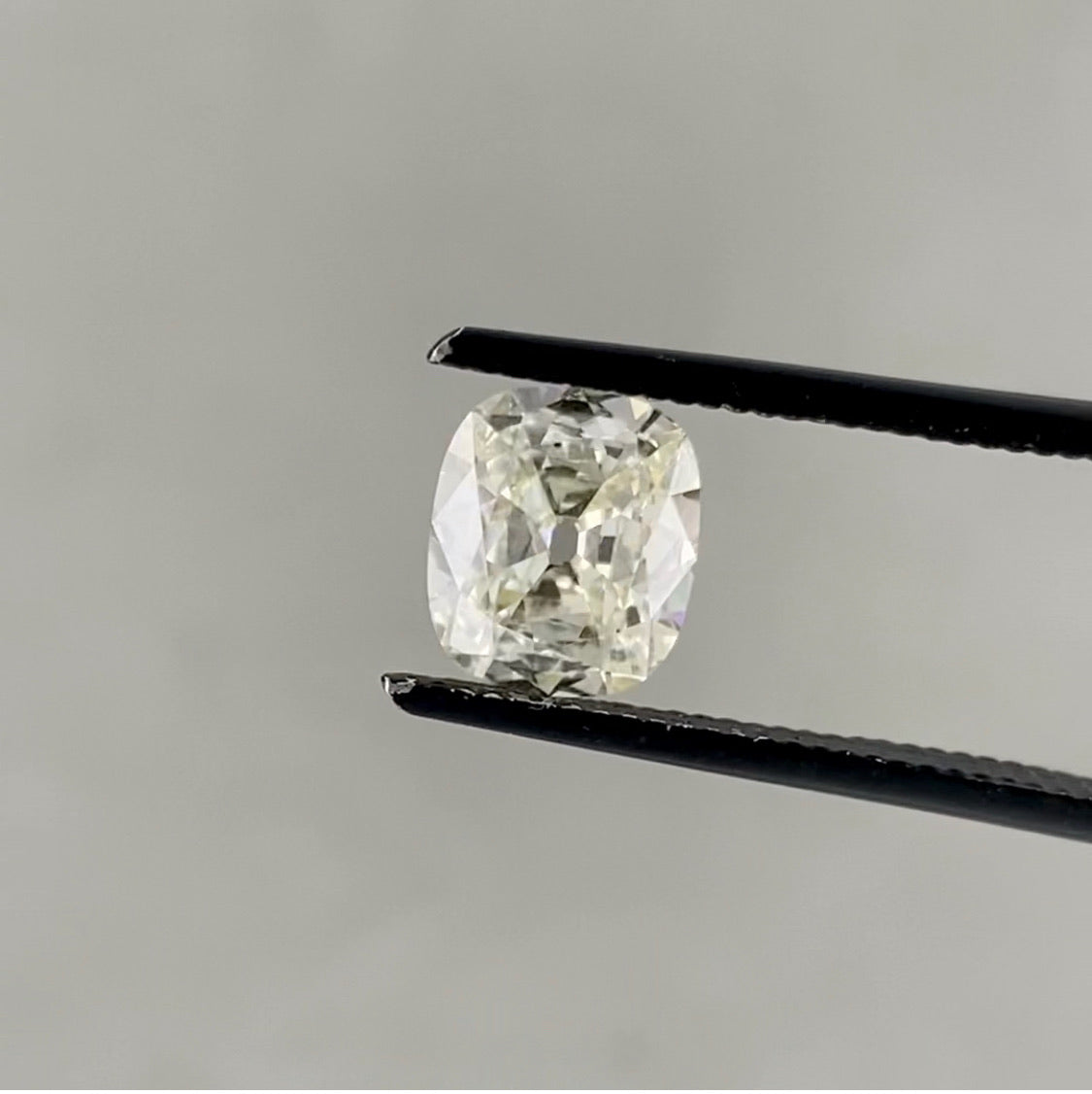 1.06ct Antique Cut Cushion L held in black diamond tweezers above a grey background