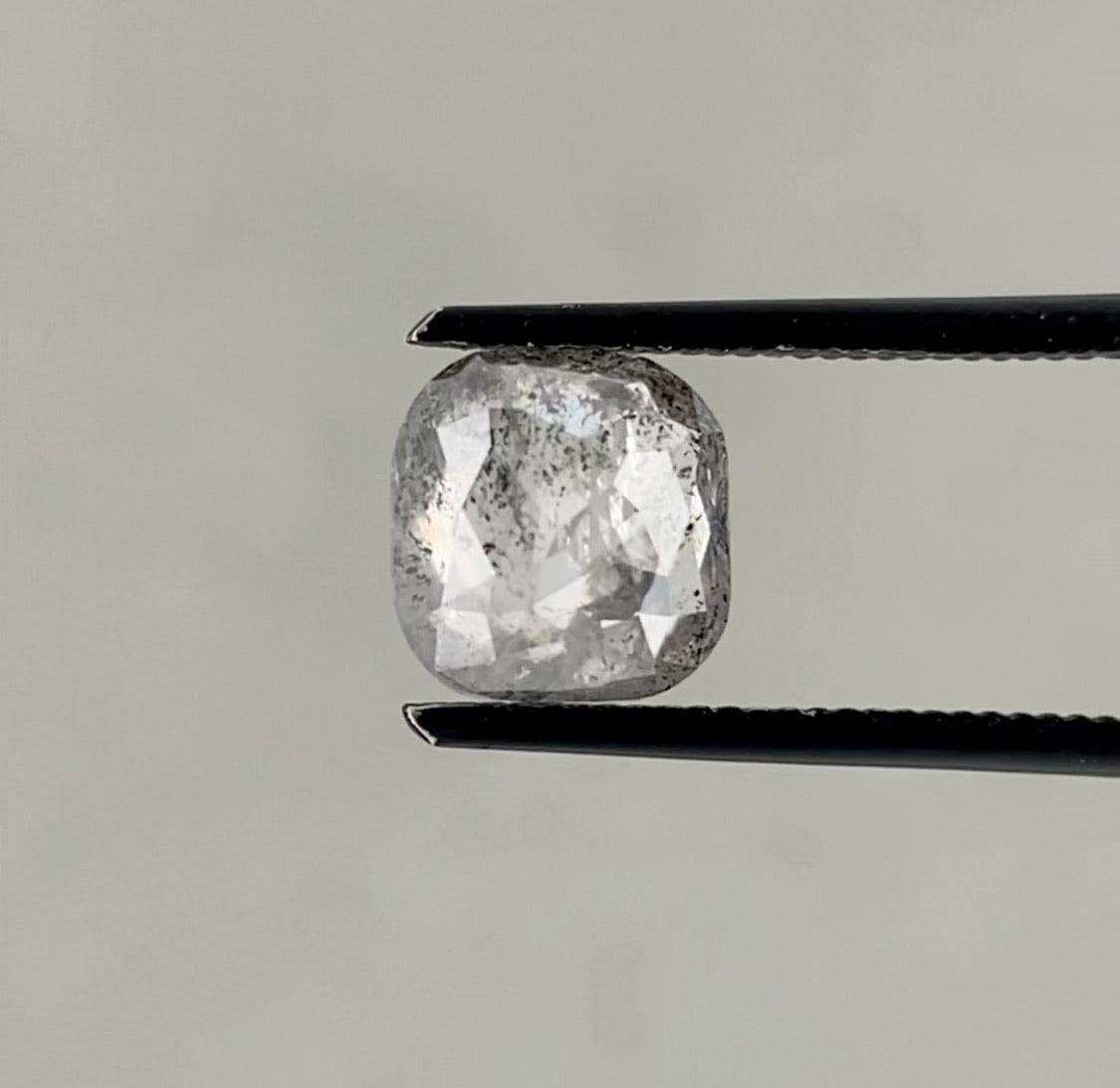 1.99ct Rose Cut Cushion Salt & Pepper held in black diamond tweezers above a grey background