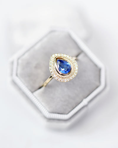 Selena Blue Sapphire Pear and Diamond Halo Engagement Ring in a ring box