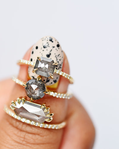 Eva Gray Octagon Diamond Engagement Ring with Pavé Diamonds shown on a thumb with other salt and pepper rings