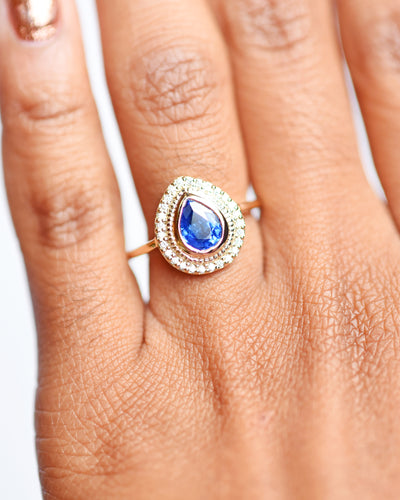 Selena Blue Sapphire Pear and Diamond Halo Engagement Ring modeled on hand
