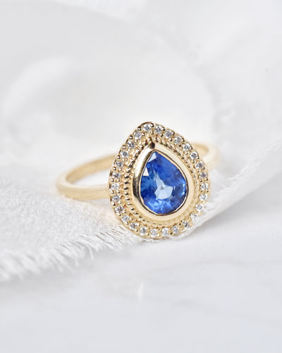 Selena Blue Sapphire Pear and Diamond Halo Engagement Ring artfully displayed