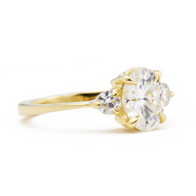 Zara Oval Three Stone Moissanite Engagement Ring viewed from the side in yellow gold
