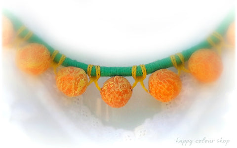 necklace with handmade orange paper mache beads on a green wrapped cord