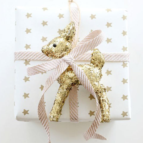 gold deer toy on baby shower gift wrapping