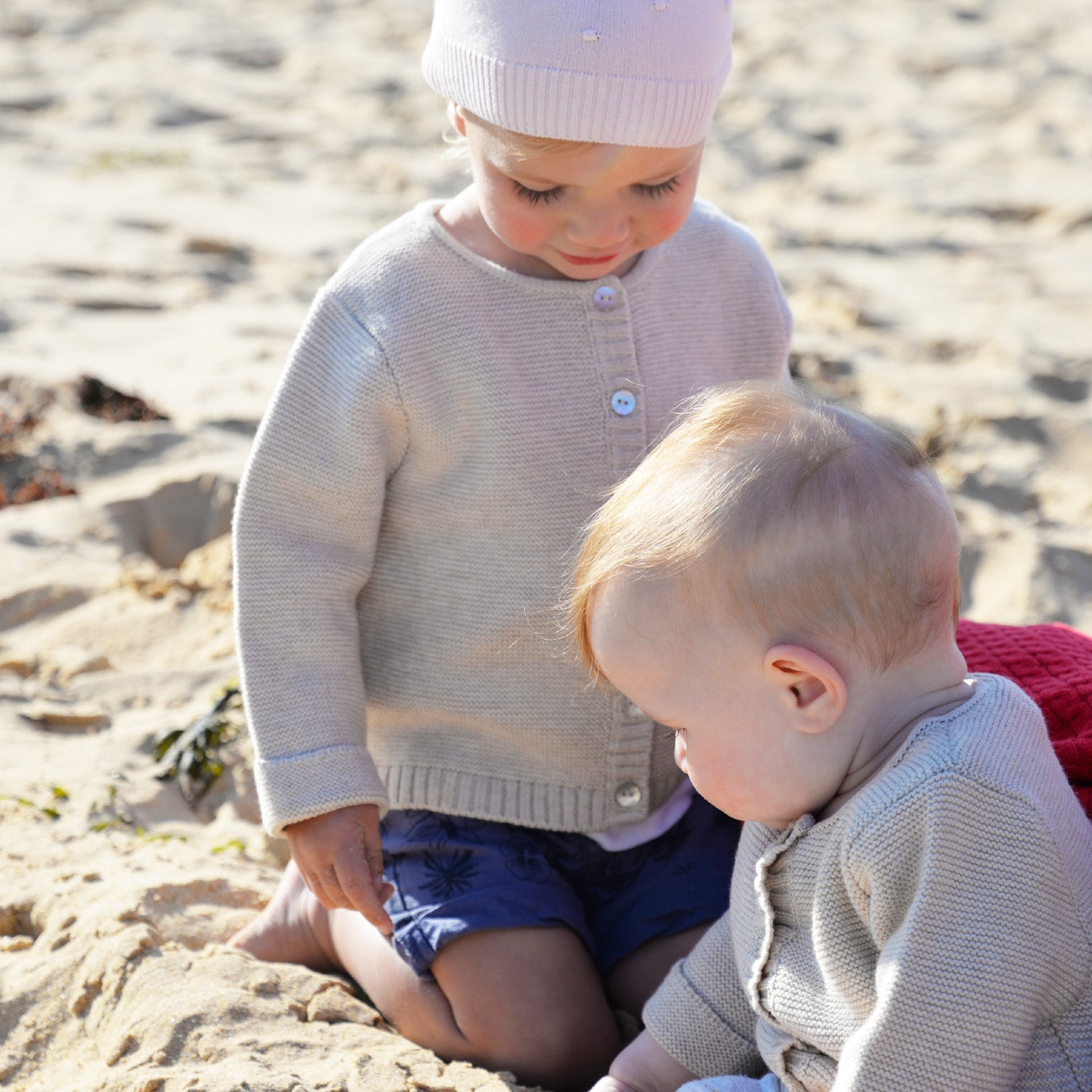 girls on beach in oatmeal baby cardigans