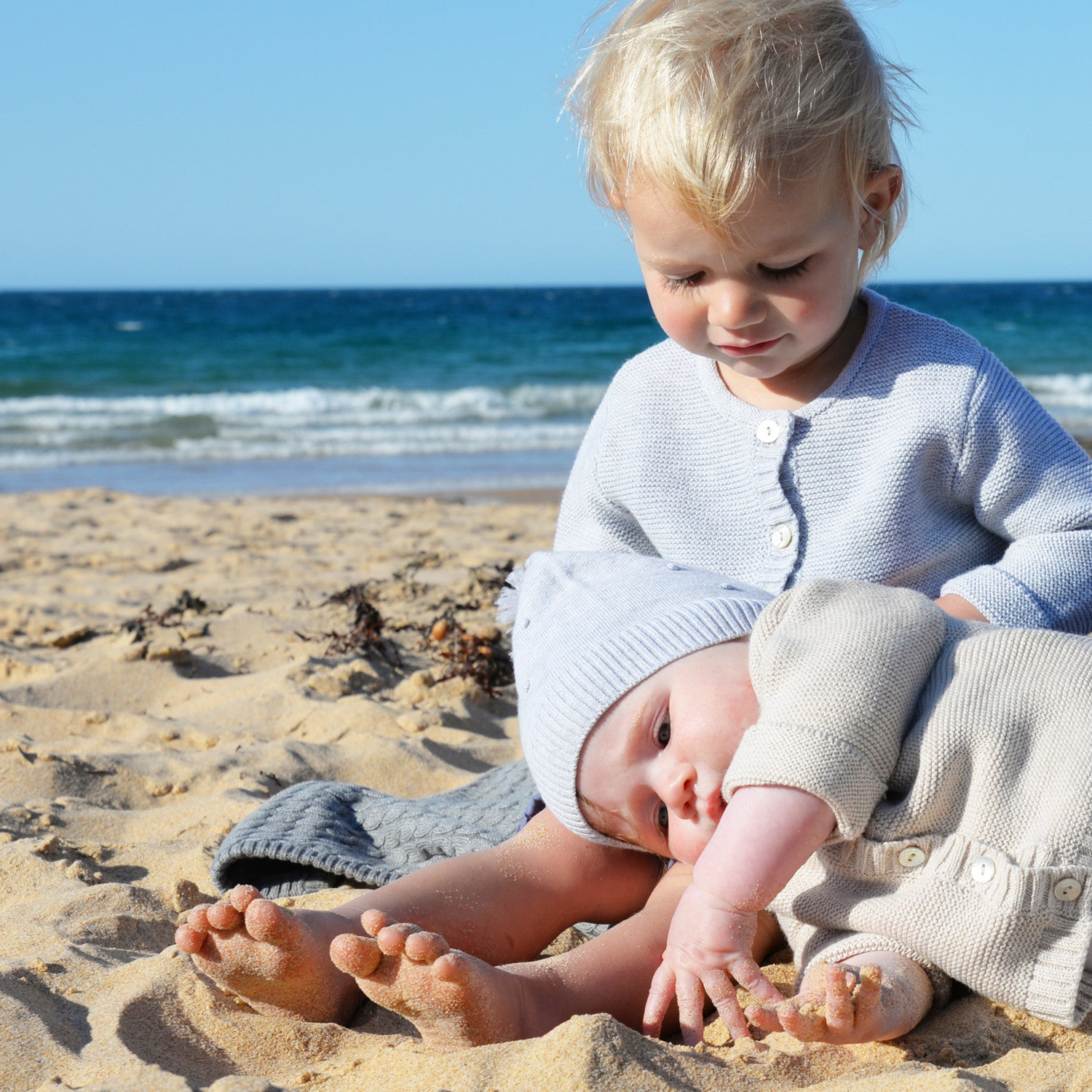 girl and baby on beach in grey marle cardigan