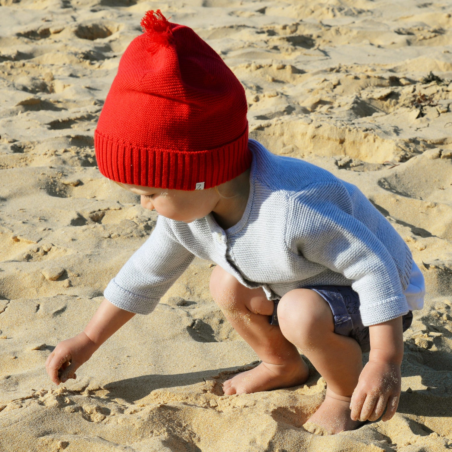 girl on beach in red beanie