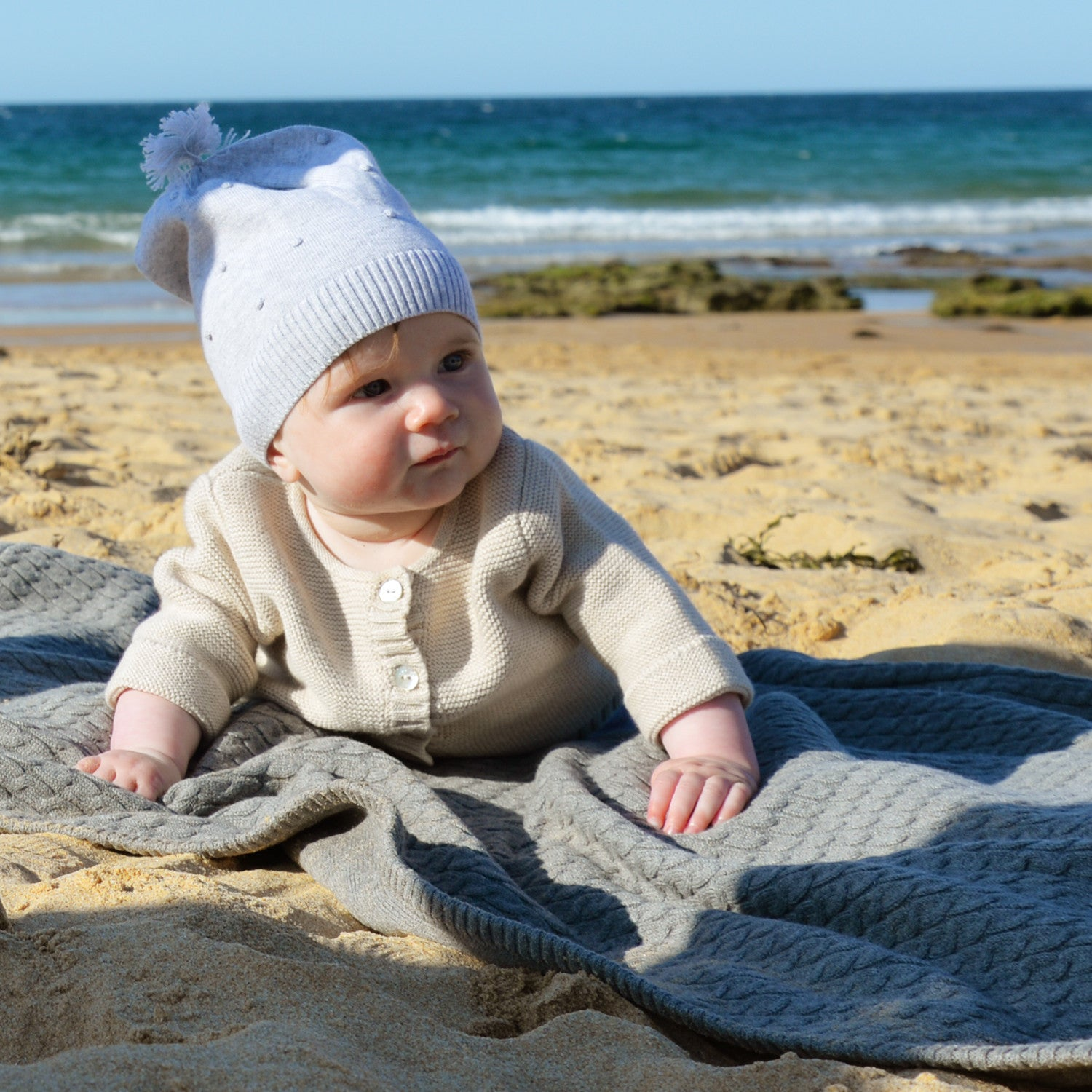 baby girl on beach in grey marle beanie