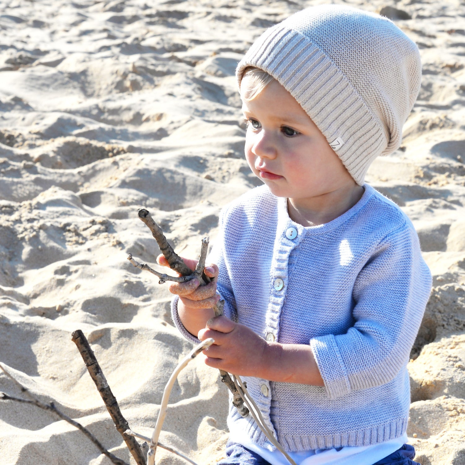 baby set oatmeal beanie on beach